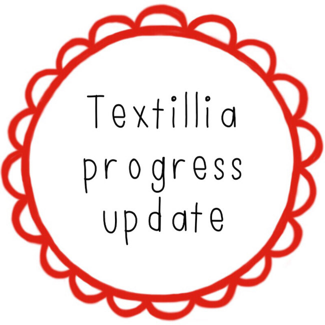 Text reading Textillia progress update in a red scalloped circle border