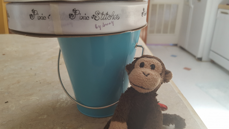 Pixie Stitches by Sway logo ribbon sitting on a small teal bucket with a plushy monkey named Playa Monkey sitting in front.