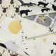 A pile of cream coloured fabrics with black and gold designs.